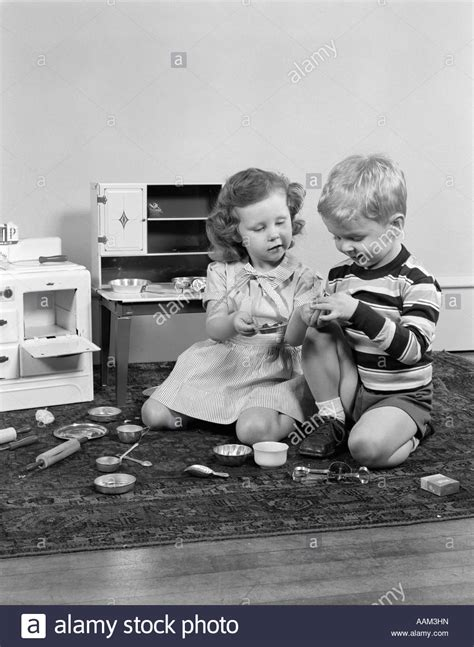 buying house with girlfriend 1950s boy girl playing house with toy stove pantry with pots pans stock photo