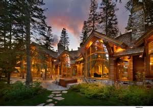 Log home exterior love the tall windows and the stone patio out front