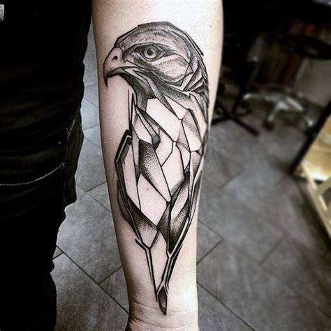 geometric eagle head tattoo on left forearm