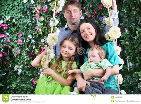 family swing happy family on swing near hedge with flowers stock photos