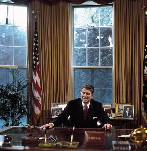 President In Office by President Ronald At His Desk In The Oval Office
