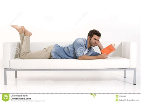 a man and a couch man on the couch reading a book stock photo image 17993580