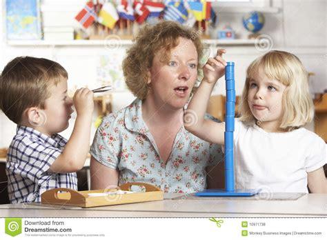 pre image helping two children at montessori pre stock