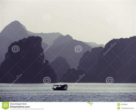 small fishing boat making ha long bay at dusk stock photo image 47248032