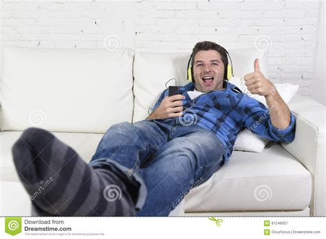 having on couch 20s or 30s man having fun listening to music with mobile