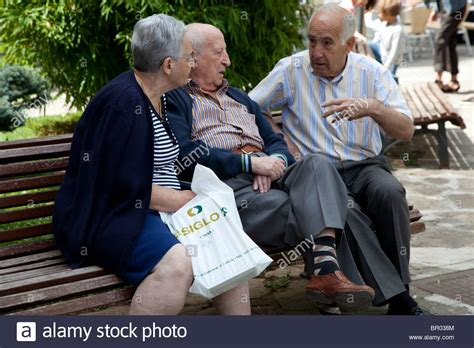old people on a bench older people chatting on park bench in jaca aragon spain