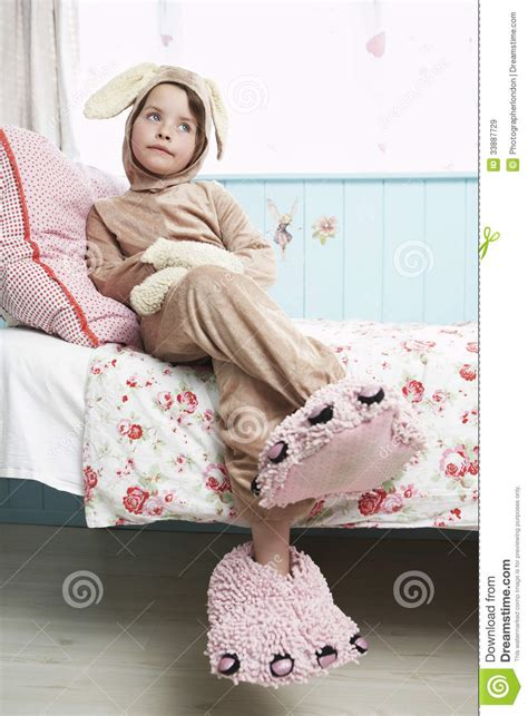 bed costume girl in bunny costume and monster slippers sitting on bed