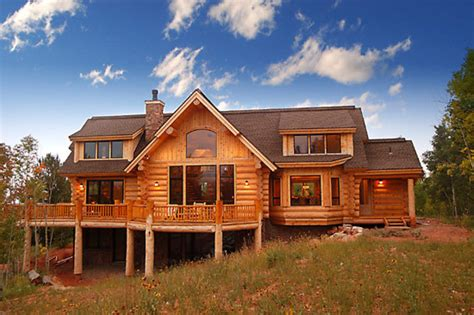 country style handcrafted log house with dormers and sun deck by sitka log homes design