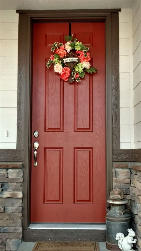 cream and chocolate brown house with burnt orange door and coral colored spring wreath front