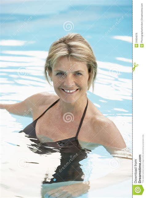 middle aged in bathing suits happy woman in swimwear swimming in pool stock photo
