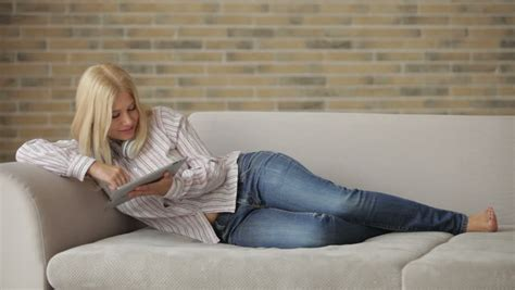 lie on couch charming girl lying on sofa using touchpad and smiling at