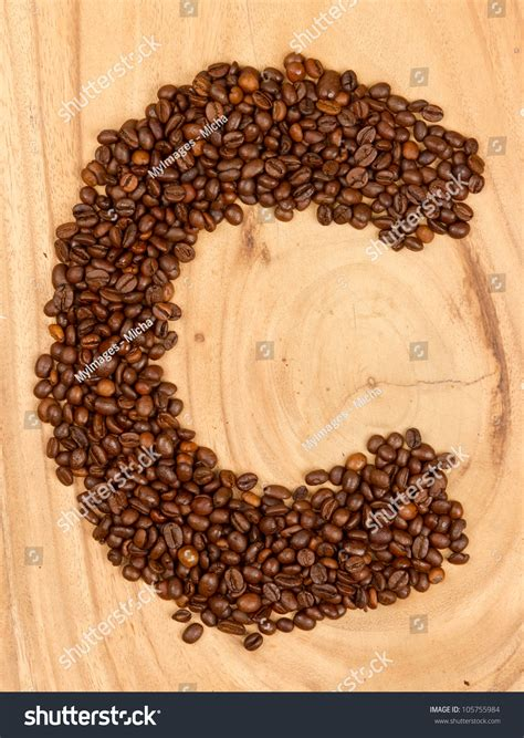letter c alphabet from coffee beans isolated on wood