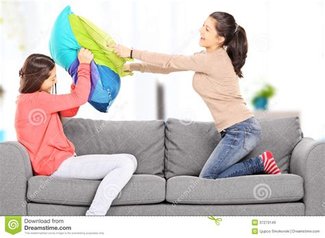 two girls having on couch two young girls having a pillow fight on sofa at home