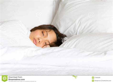 tucked in bed only show face woman in white blanket tucked sleep on the