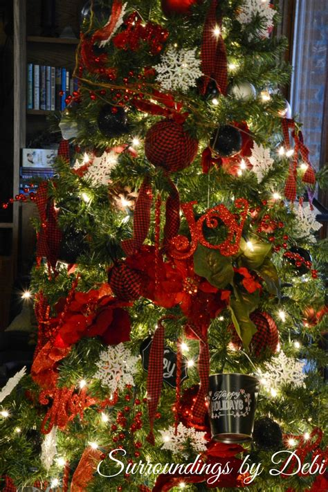 picture of a christmas tree with a red scarf aroud the top tree in and black surroundings by debi