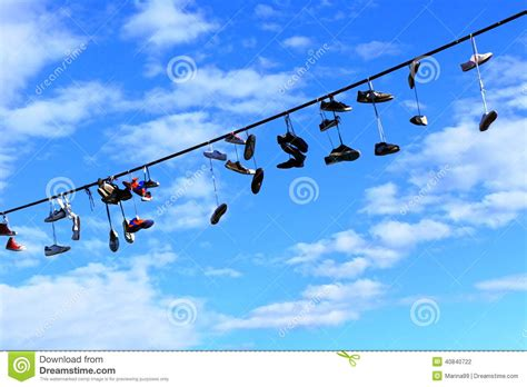 hanging photos on wire old shoes hanging on electrical wire against a blue sky