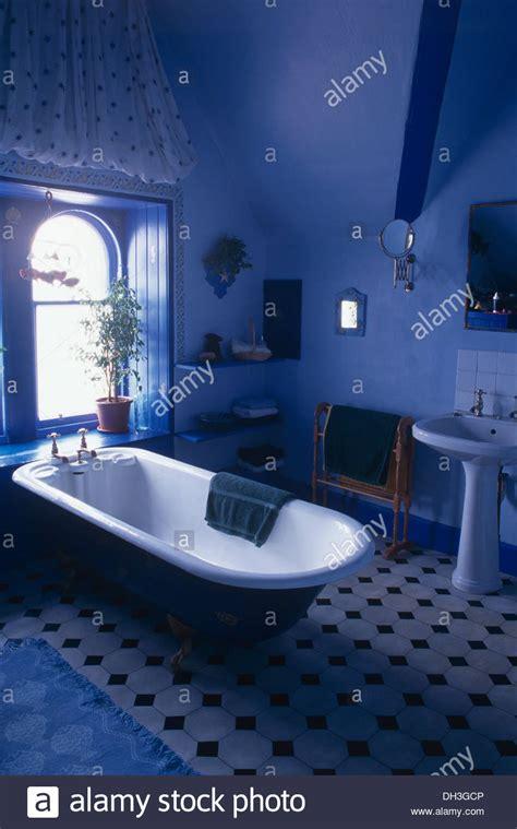 black white blue bathroom roll top bath below window in bright blue bathroom with