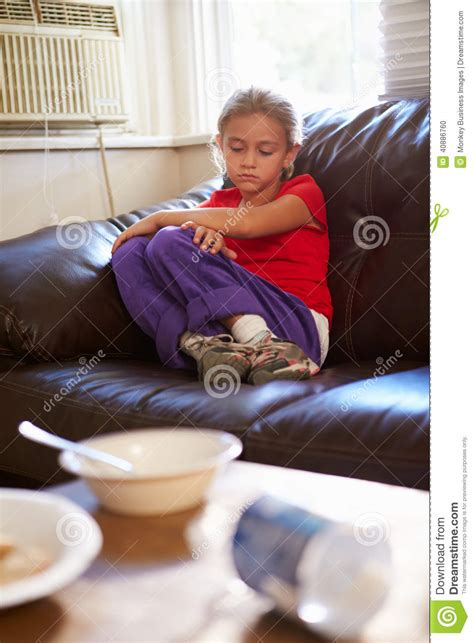 girl sitting on couch unhappy girl sitting on sofa at home stock photo image