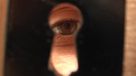 men peeping through a keyhole