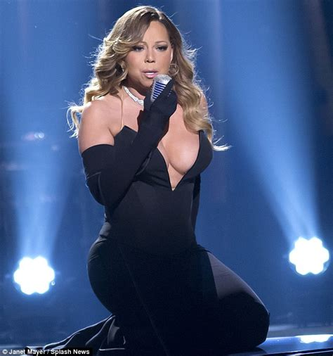 mariah carey sizzles in a very low cut gown as she poses