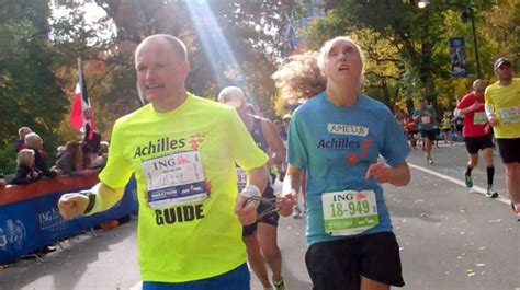 Run With The Blind runners with disabilities guiding a blind runner in the