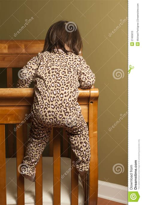 baby climbing out of crib climbing out of the crib stock photo image 27465810