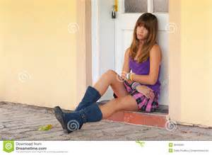Cute sad teenage girl sitting in front of the door stock image image