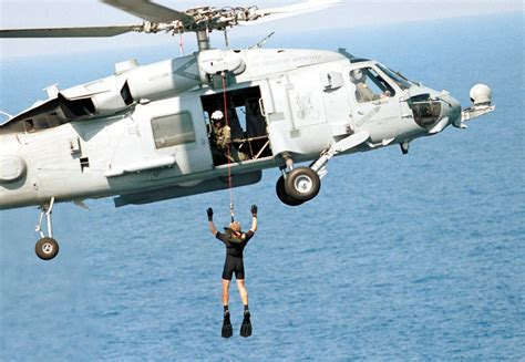 Us Navy Search File Us Navy 001006 N 3896h 001 Search And Rescue Swimmer Is Lowered From A Helicopter