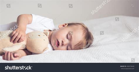 sleeping with baby in bed baby sleeping crib peaceful baby lying stock photo