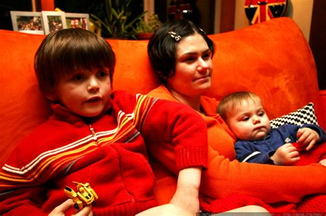 curled up on the couch mother and sons curled up on the couch watching a movie
