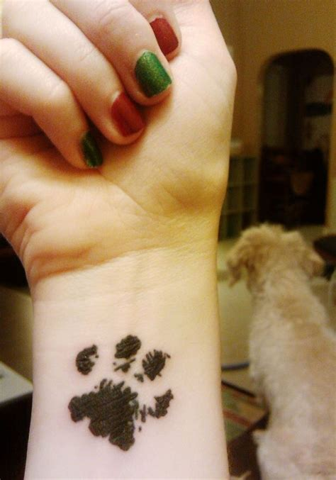 footprint tattoos on wrist black paw on wrist