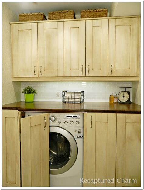 concealed washer and dryer laundry room with light wood cabinets and hidden washer