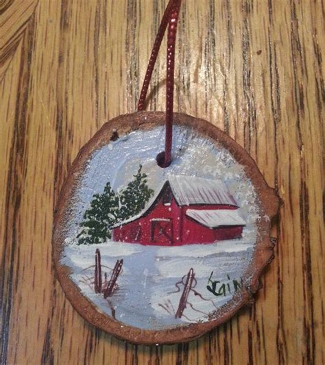 this wood slice ornament is hand painted with an old red