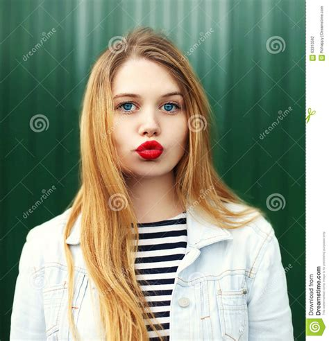 blonde girl with red lipstick blonde young girl with red lipstick blowing lips stock
