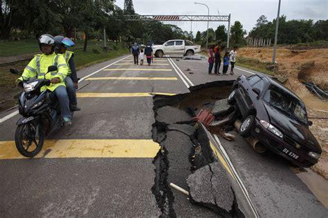road ban new year 2014 malaysia ride past a road damaged by flooding at kuala krai