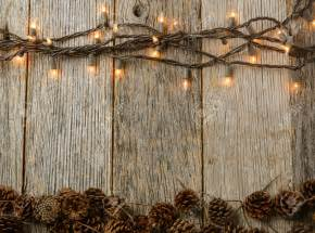 rustic light lights and pine cones on rustic wood background