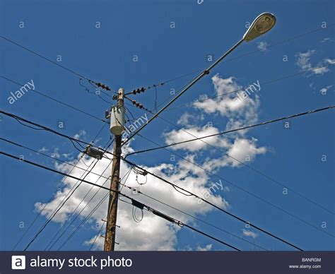 electric street light pole power utility and street light pole with wires clouds