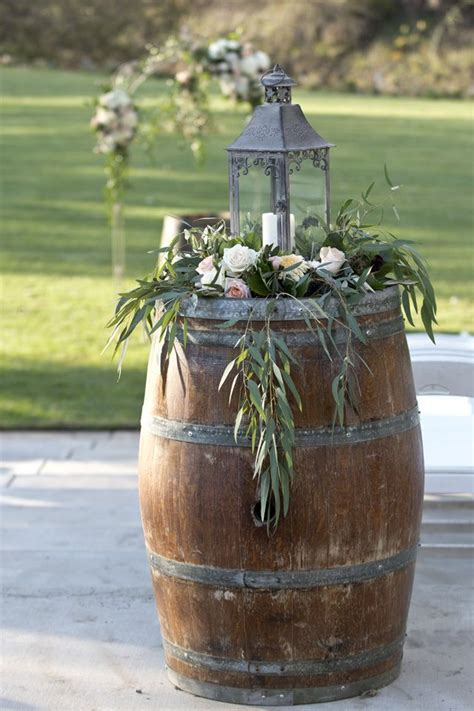 Lantern with hanging greens on wine barrel. Lori Makabe