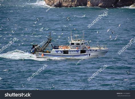 small boat cost small fishing boat sailing near coast stock photo