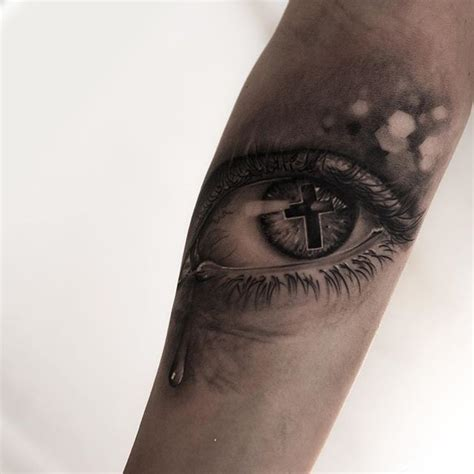 cross tattoo by eye cross in tearful eye on arm by niki norberg