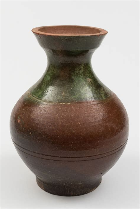 a brown and green glazed pottery vase and