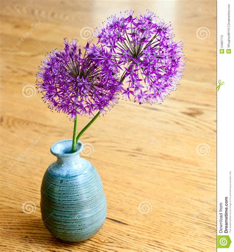 purple flowers in a blue clay vase stock photography