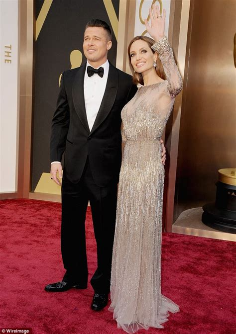brad pitt holds tight to angelina jolie on oscars 2014 red