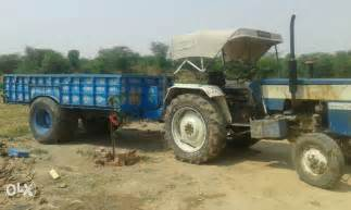 Black and blue swraj 735 fe 1995 model tractor and trolli for sale