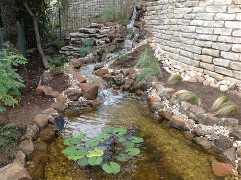 todd s landscaping todd s pond and waterfall through the retaining wall rustic landscape by