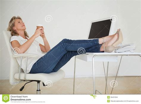 5 ft office desk casual businesswoman having a coffee with her feet up at