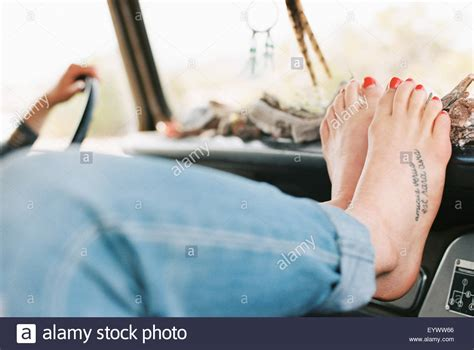 tattoo photo stock barefoot woman resting her feet on the dashboard of a 4x4
