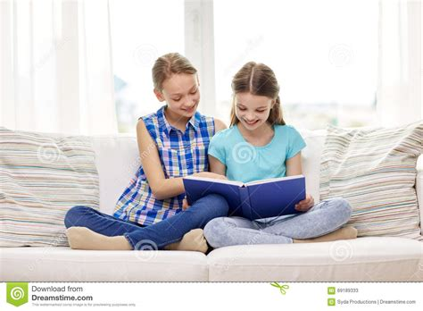 people having on a couch two happy girls reading book at home stock image image