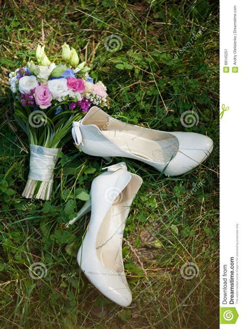 Pair Of White Ladies Shoes On Grass And Beautiful Bouquet