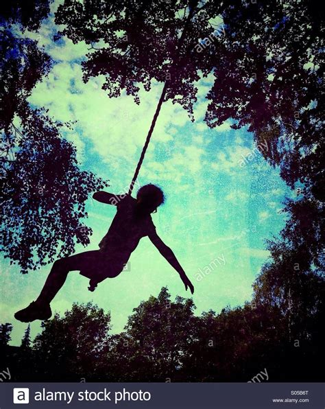 silhouette swing girl on rope swing in silhouette against sky stock photo